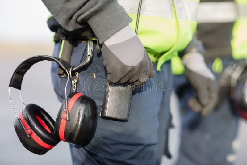 Mittelteil der Arbeitskraft mit den Gehörschützern befestigt zur Hose stockfoto