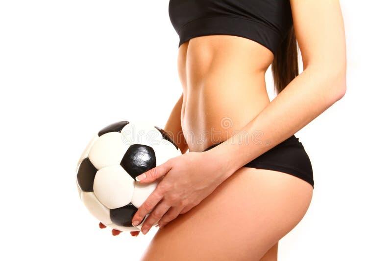 Mittelteil der Sitzfrau in der Sportkleidung mit Fußballstellung stockfoto