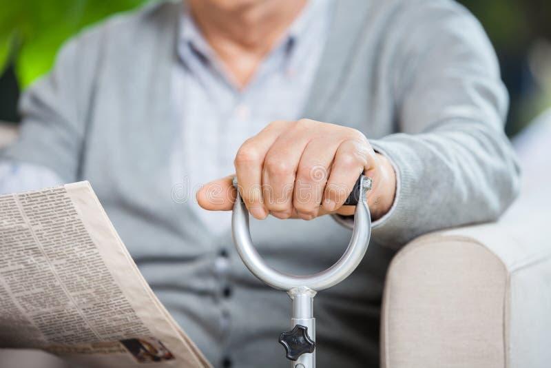 Mittelteil des älteren Mannes mit Zeitung und Stock lizenzfreie stockbilder