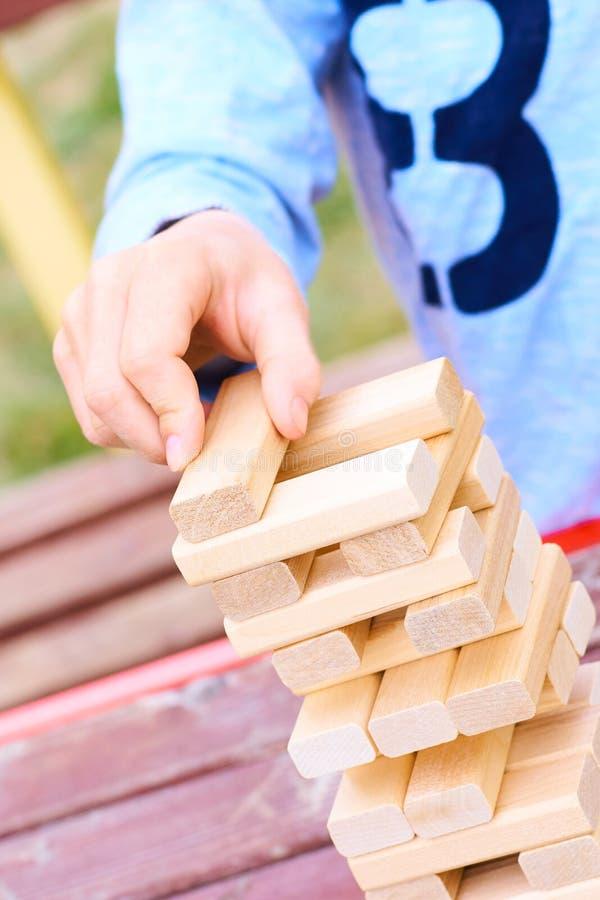 Mittelteil des Kindes, das Turmspiel der hölzernen Blöcke für das Üben der körperlichen und Geistesfähigkeit spielt lizenzfreies stockbild
