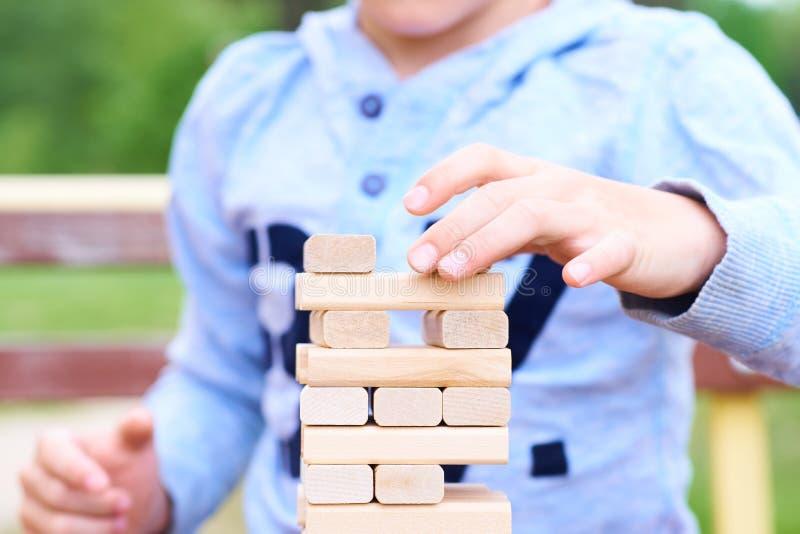 Mittelteil des Kindes, das Turmspiel der hölzernen Blöcke für das Üben der körperlichen und Geistesfähigkeit spielt lizenzfreie stockfotografie