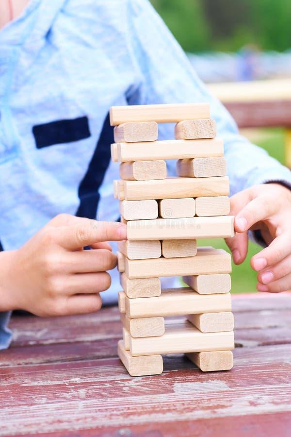 Mittelteil des Kindes, das Turmspiel der hölzernen Blöcke für das Üben der körperlichen und Geistesfähigkeit spielt lizenzfreie stockfotos