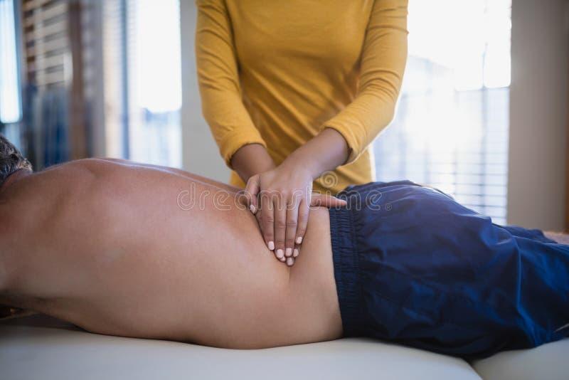 Mittelteil des weiblichen Therapeuten Rückenmassage gebend dem hemdlosen männlichen Patienten, der auf Bett liegt lizenzfreie stockbilder