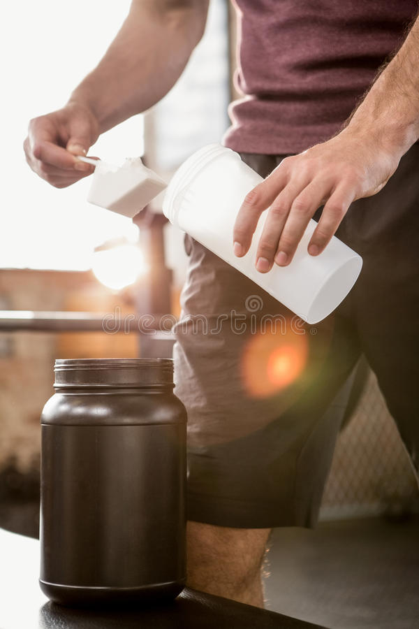 Mittelteil eines muskulösen Mannes, der Ergänzung Flasche hinzufügt stockbilder