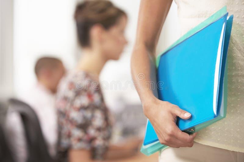 Mittelteil von Geschäftsfrau-Carrying Folder With-Kollegen hinten lizenzfreies stockfoto