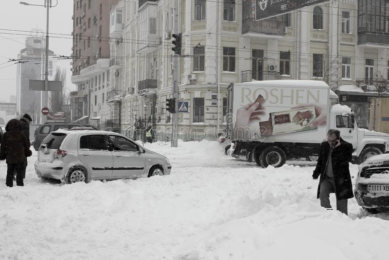 Mitten av staden som paralyseras av snöfallet och chaufförerna, hjälper sig arkivbilder
