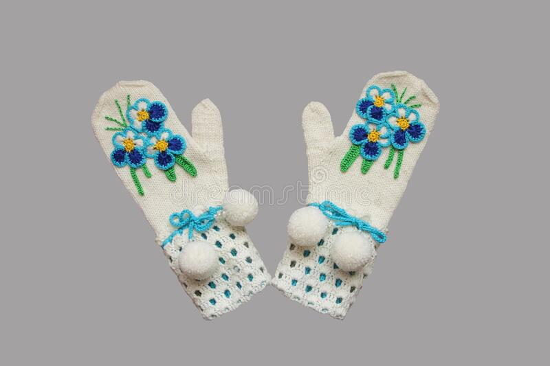 Mittens knitted from white yarn stock image