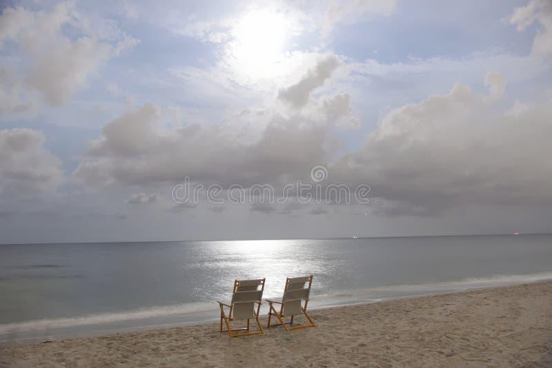 Mitternacht auf einem Florida-Strand mit den Stühlen bereit zu ihren romantischen Inhabern lizenzfreies stockbild