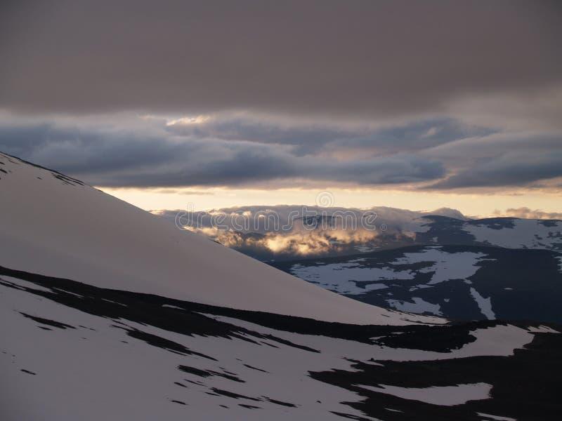 Mitternachtssonne über den schneebedeckten Bergen stockfoto