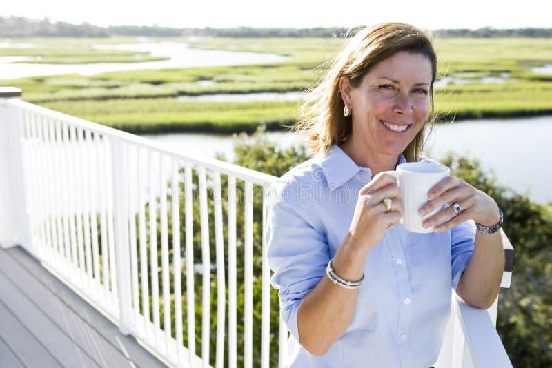Mittler-Erwachsener Frau, die Tasse Kaffee auf Terrasse hat lizenzfreies stockbild