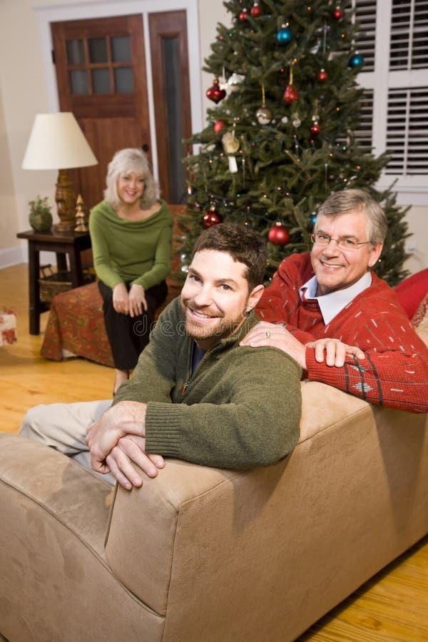Mittler-Erwachsener Mann und ältere Muttergesellschaft durch Weihnachtsbaum lizenzfreies stockbild