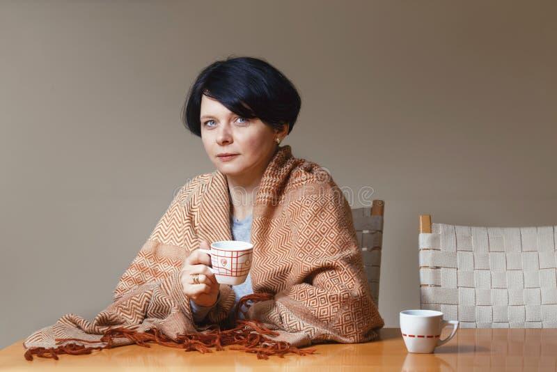 Mittlere Altersfrau des Brunette bedeckt mit der Decke, die bei Tisch trinkenden Teekaffee sitzt lizenzfreies stockfoto