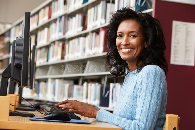 Mittlere Altersfrau, die an Computer in der Bibliothek arbeitet lizenzfreies stockbild