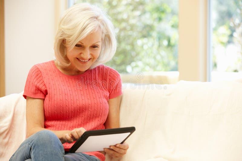 Mittlere Altersfrau, die zu Hause Tablette verwendet stockfotografie