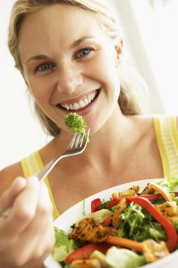 Mittlere erwachsene Frau, die einen gesunden Salat isst stockfoto