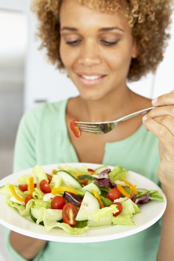 Mittlere erwachsene Frau, die einen gesunden Salat isst stockfotos