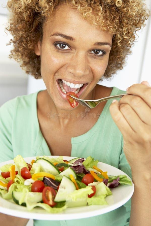 Mittlere erwachsene Frau, die einen Salat isst stockfotografie