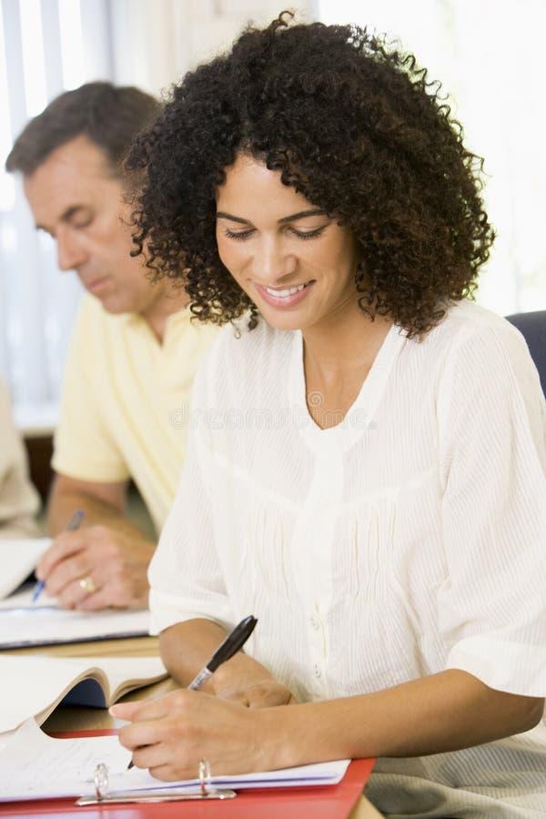 Mittlere erwachsene Frau, die mit anderen erwachsenen Kursteilnehmern studiert lizenzfreies stockfoto