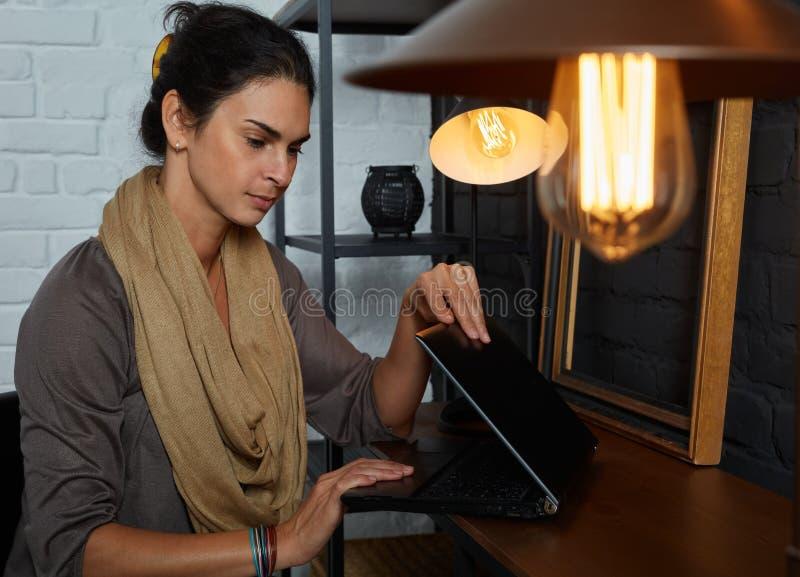 Mittlere erwachsene Frau, die zu Hause mit Laptop arbeitet lizenzfreie stockfotos