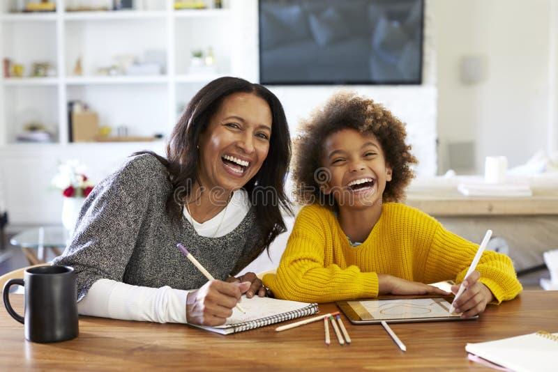 Mittlere gealterte Afroamerikanerfrau, die bei Tisch in ihrer Esszimmerzeichnung mit ihrer jugendlichen Enkelin, lachend zum came lizenzfreies stockbild