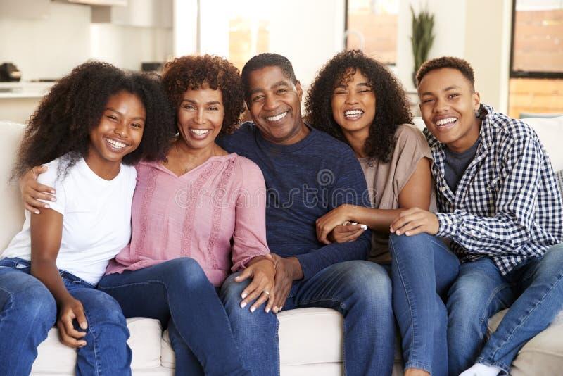 Mittlere gealterte Eltern, die zu Hause mit ihren jugendlich und jungen erwachsenen Kindern, lächelnd zur Kamera sitzen lizenzfreies stockfoto