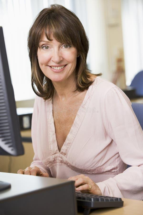 Mittlere gealterte Frau auf einem Computer lizenzfreie stockfotografie