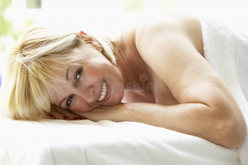Mittlere gealterte Frau, die auf Massage-Tabelle sich entspannt stockfotos