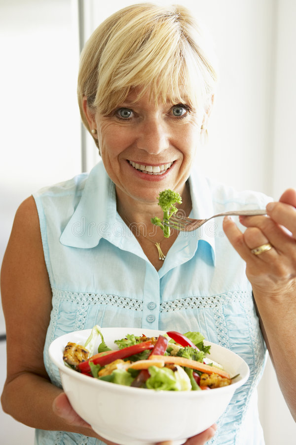 Mittlere gealterte Frau, die einen gesunden Salat isst lizenzfreies stockfoto