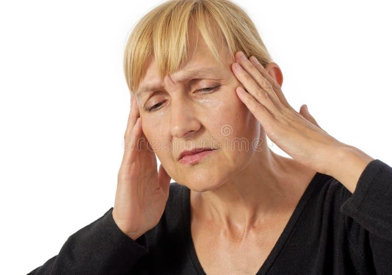 Mittlere gealterte Frau, die Kopfschmerzen hat lizenzfreie stockfotografie