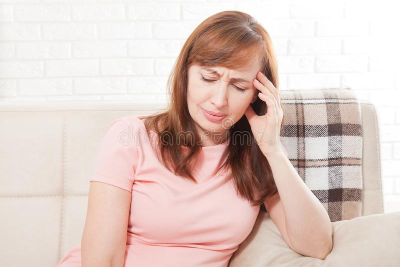 Mittlere gealterte Frau, die Kopfschmerzen hat Wohnliches Konzept Menopause und Krise Kopieren Sie Platz lizenzfreie stockbilder