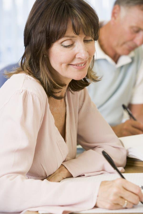 Mittlere gealterte Frau, die mit anderen Kursteilnehmern studiert lizenzfreies stockfoto