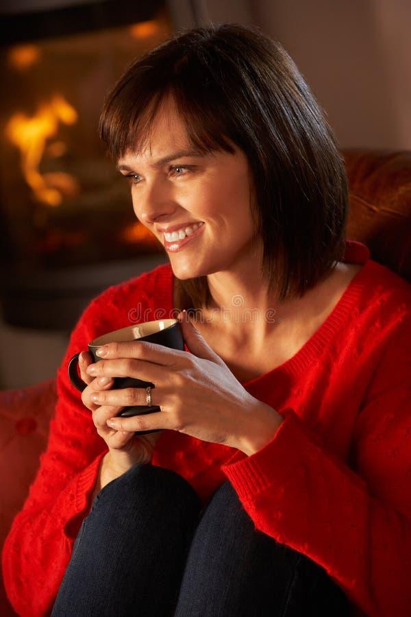 Mittlere gealterte Frau, die mit heißem Getränk sich entspannt stockbild