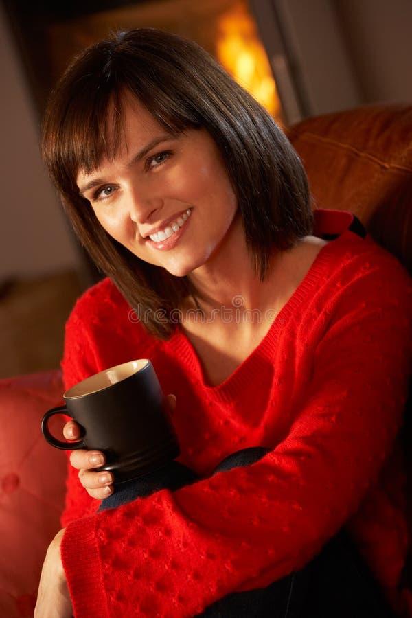 Mittlere gealterte Frau, die mit heißem Getränk sich entspannt lizenzfreies stockfoto
