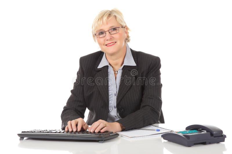 Mittlere gealterte Geschäftsfrau im Büro lizenzfreie stockfotografie