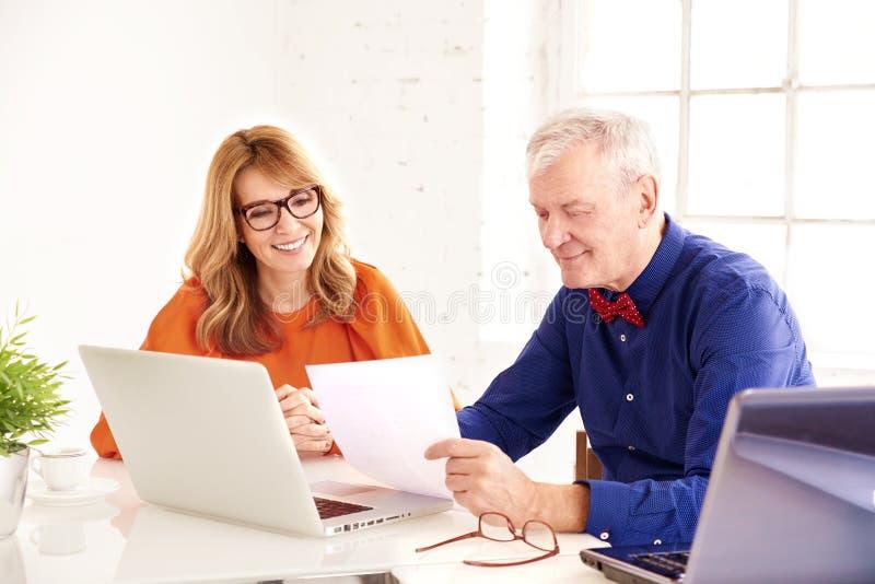 Mittlere gealterte Geschäftsfrau und älterer Geschäftsmann, die zusammen an Laptop im Büro arbeitet stockfotos