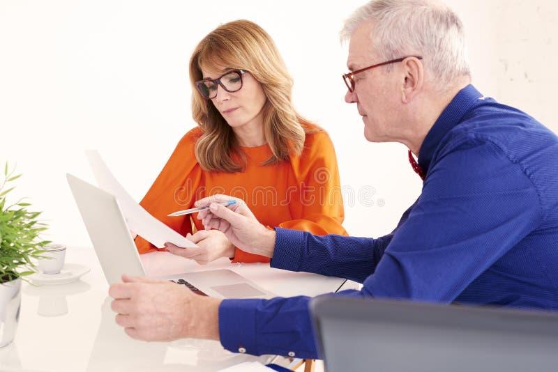 Mittlere gealterte Geschäftsfrau und älterer Geschäftsmann, die zusammen an Laptop im Büro arbeitet stockbild