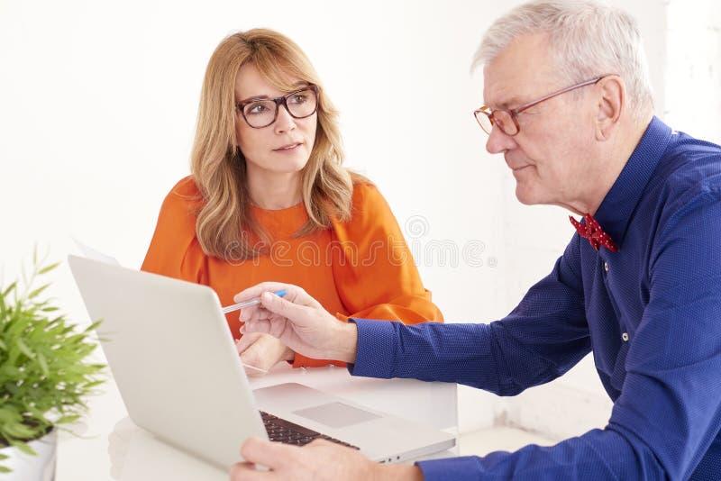 Mittlere gealterte Geschäftsfrau und älterer Geschäftsmann, die zusammen an Laptop im Büro arbeitet stockfotografie
