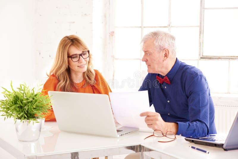 Mittlere gealterte Geschäftsfrau und älterer Geschäftsmann, die zusammen an Laptop im Büro arbeitet lizenzfreies stockbild