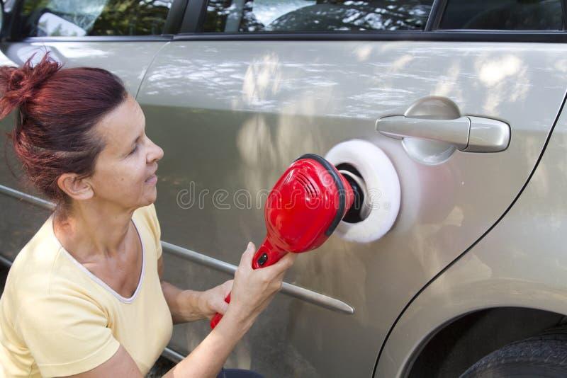Mittlere gealterte nette Frau, die ihr Auto poliert stockbild