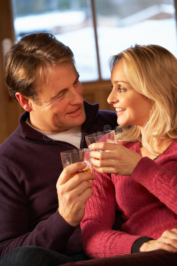 Mittlere Gealterte Paare Auf Sofa Mit Whisky Lizenzfreie Stockbilder