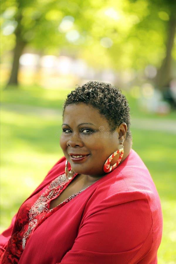 Mittlere gealterte schwarze Frauen-Park-Rot-Jacke lizenzfreie stockfotografie
