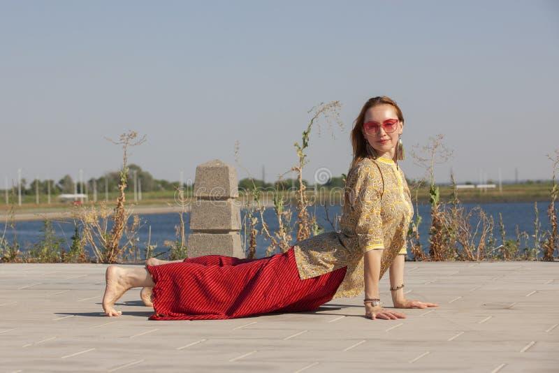Mittlere Greisin, die fr?h Yoga morgens in einem Park tut stockbilder