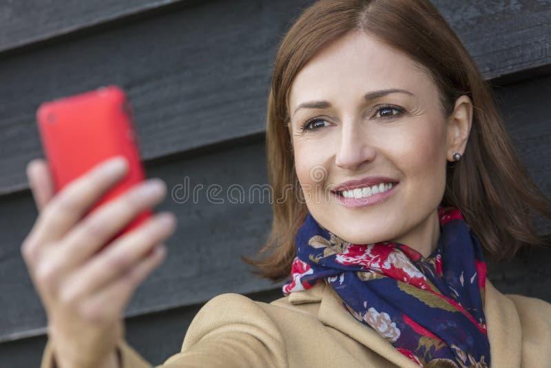 Mittlere Greisin, die Handy Selfie nimmt stockfoto