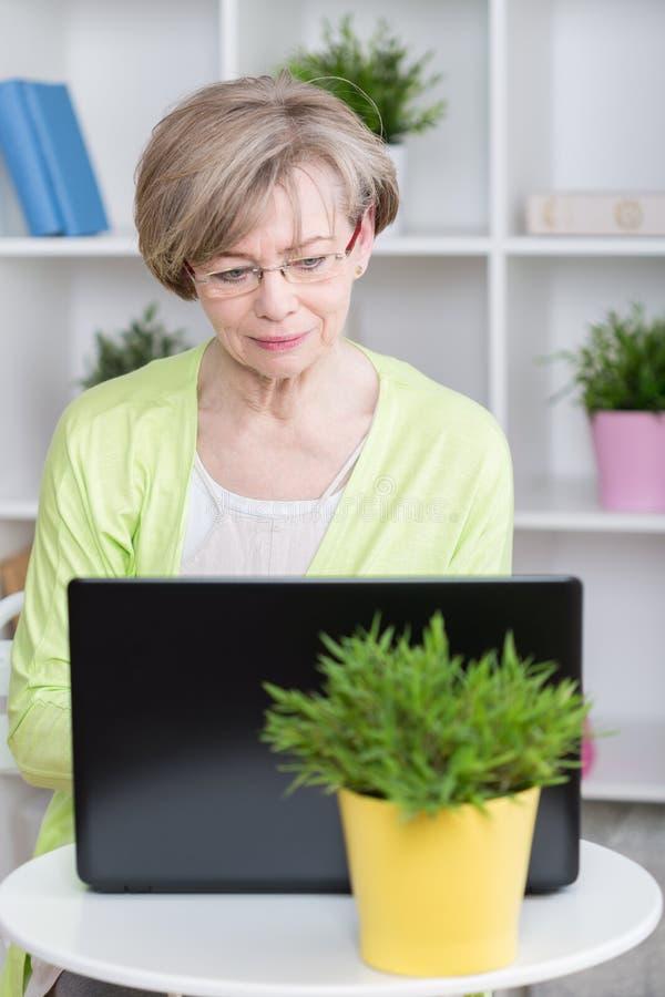 Mittlere Greisin, die Laptop verwendet stockfoto