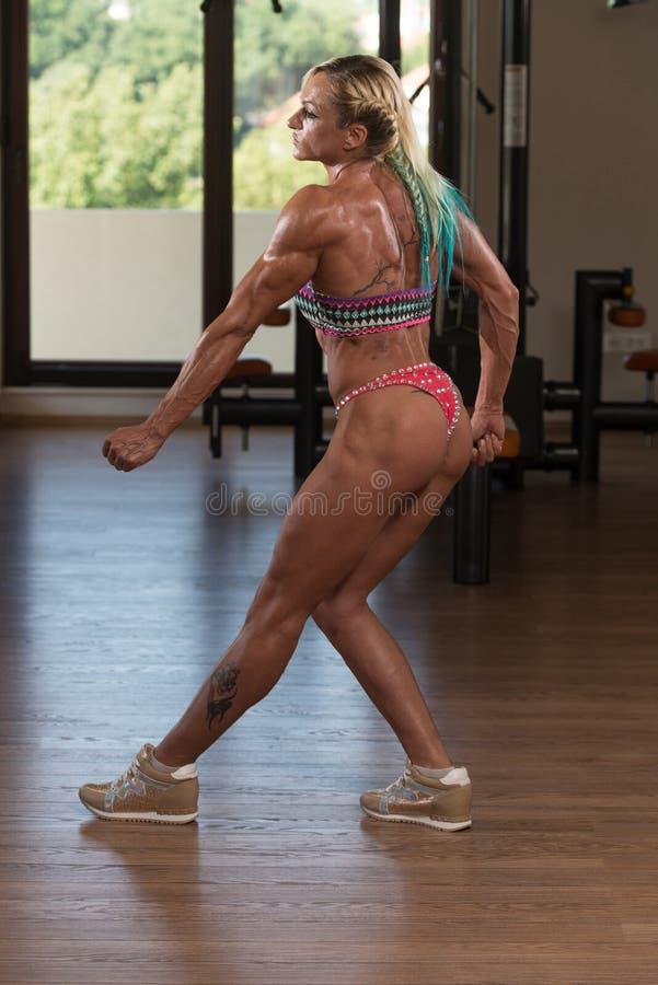 Mittlere Greisin, die Muskeln in der Turnhalle biegt stockbilder