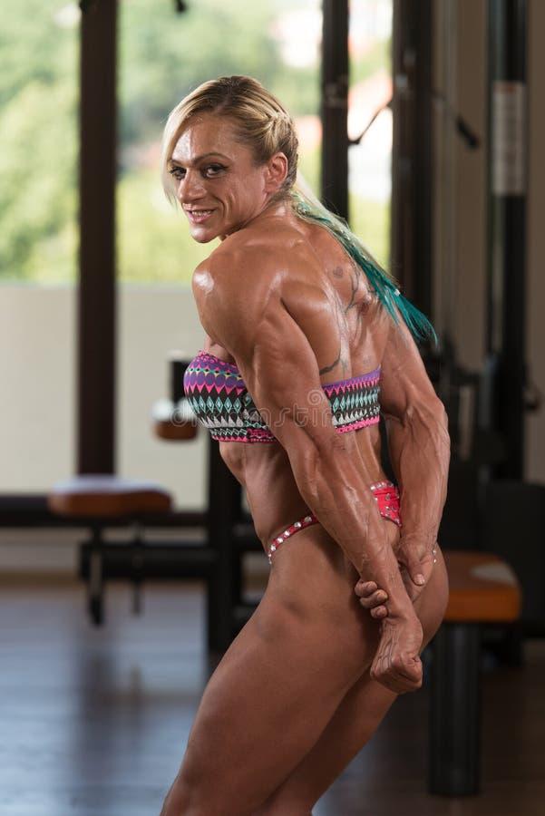 Mittlere Greisin, die Muskeln in der Turnhalle biegt lizenzfreies stockbild