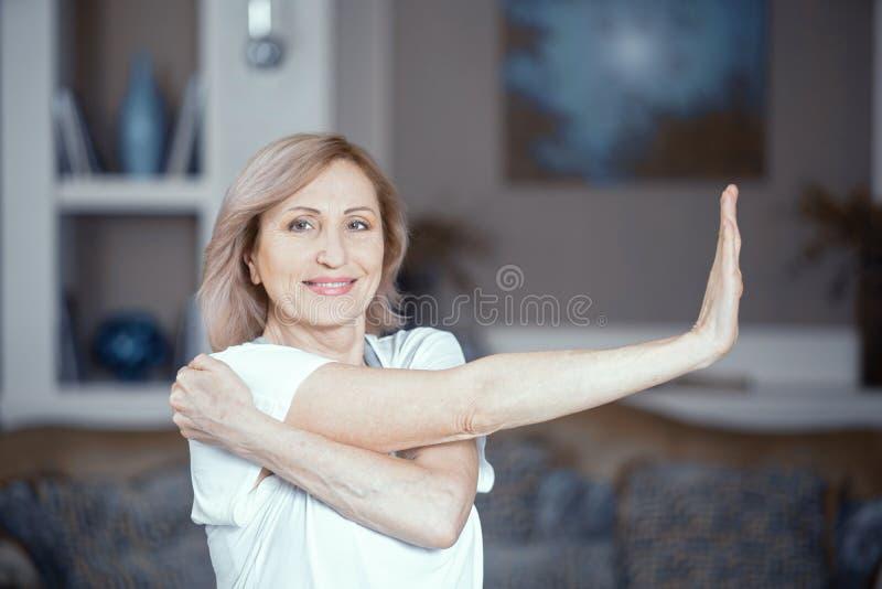 Mittlere Greisin, die zu Hause Yoga tut stockfotos