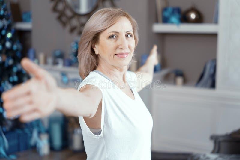 Mittlere Greisin, die zu Hause Yoga tut stockfoto