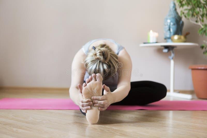 Mittlere Greisin, die zuhause Yoga tut lizenzfreies stockfoto