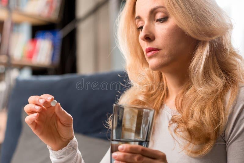 Mittlere Greisin Glas zu Hause halten mit Wasser und Pille lizenzfreies stockfoto